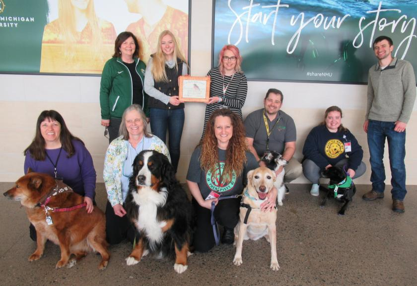Pictured are: (front row from left) Pet Partners Ann Dausey, Kelly December and Tanya Savage with their dogs; and (back row from left) health fair committee member Sharon Carey, Health Promotion Society President Haley Anderson, Pet Partner Kim Benson-Custard (holding the award), Rick Custard, Bethany Rudness, and health fair committee member Matt Kilgas.