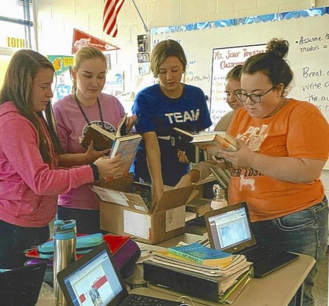 Students in Townsend's classroom review the books donated by NMU.