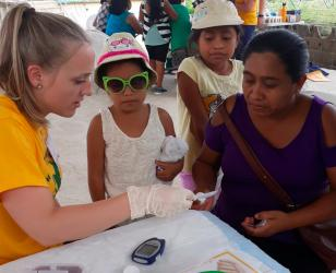 NMU community health graduate Erin Messerschmidt at a community health fair in Belize, May 2019.